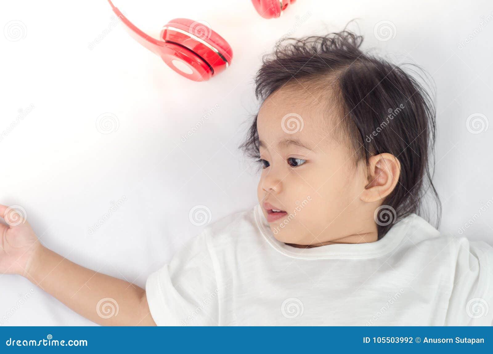 Fille asiatique d enfant en bas âge se trouvant sur le lit à la maison