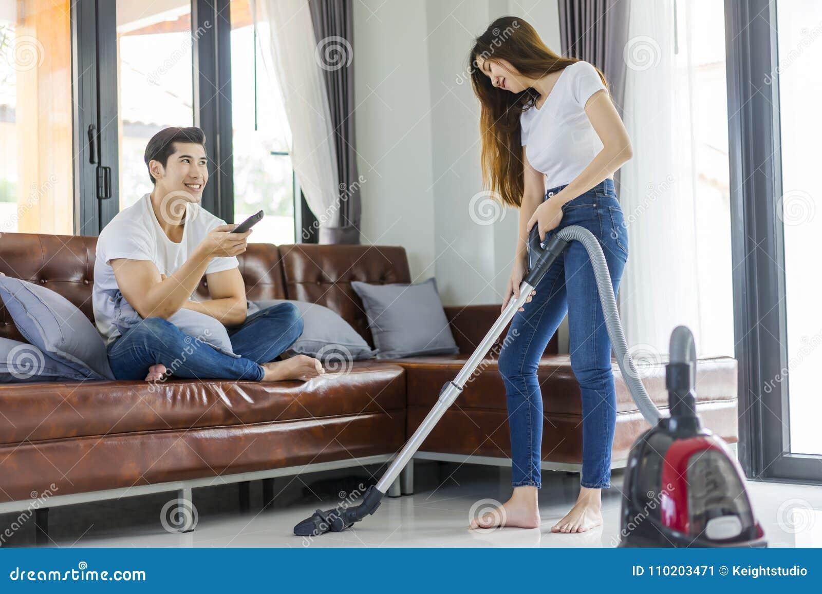 Fille asiatique de couples faisant le nettoyage de plancher avec le whil de décapant de vaccuum