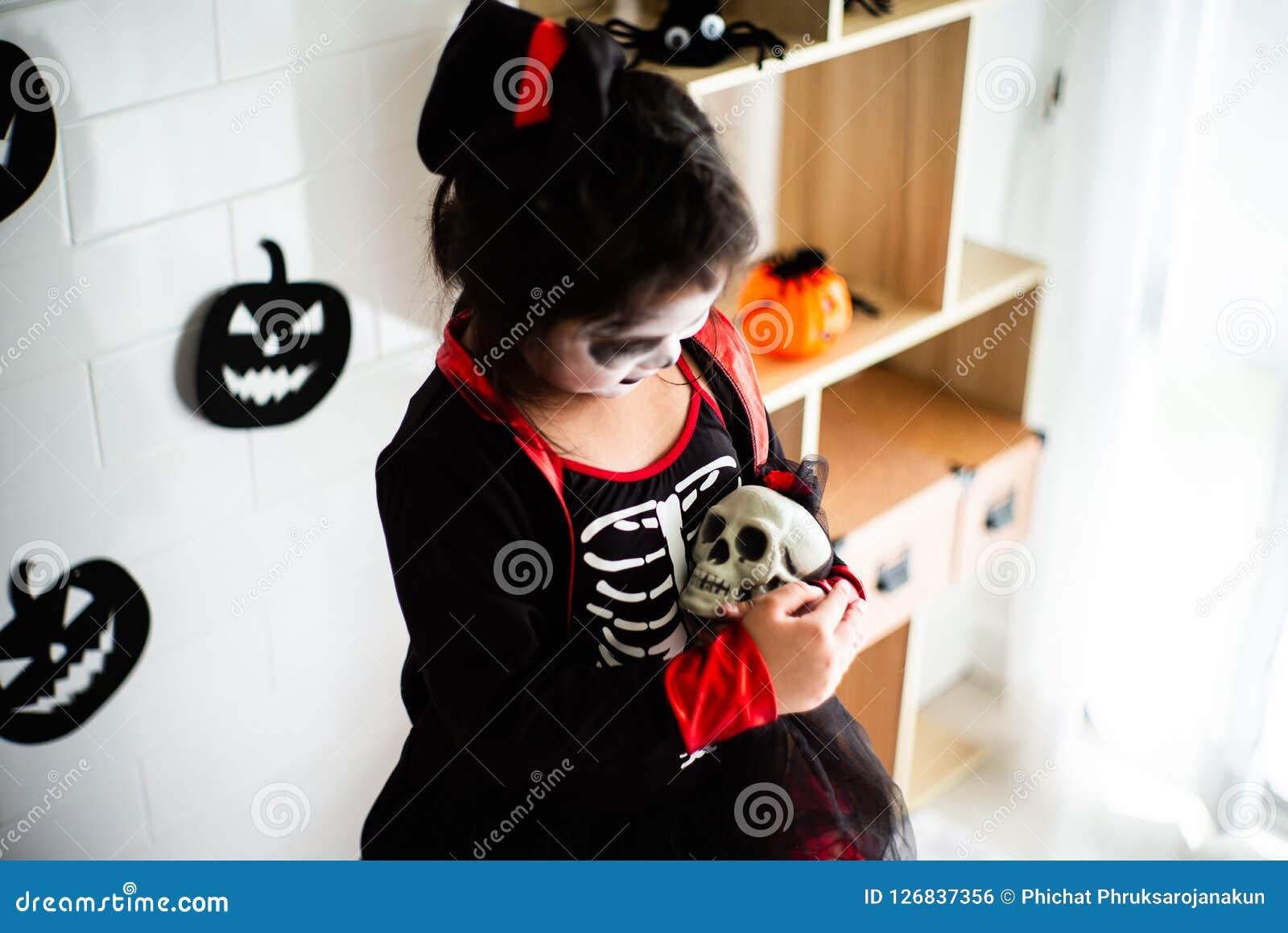 Fille asiatique de portrait petite dans le costume de Halloween tenant le skul