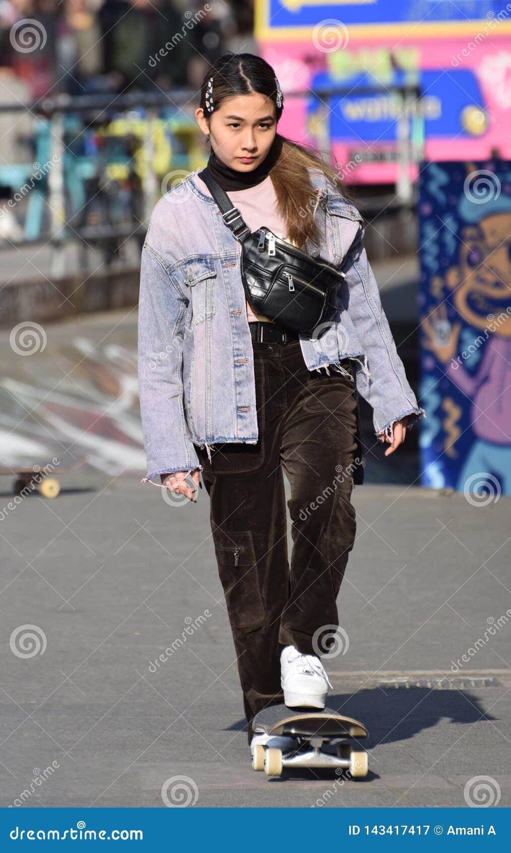 Fille asiatique faisante de la planche à roulettes de jeunes à la mode Londres, R-U Mars 2019