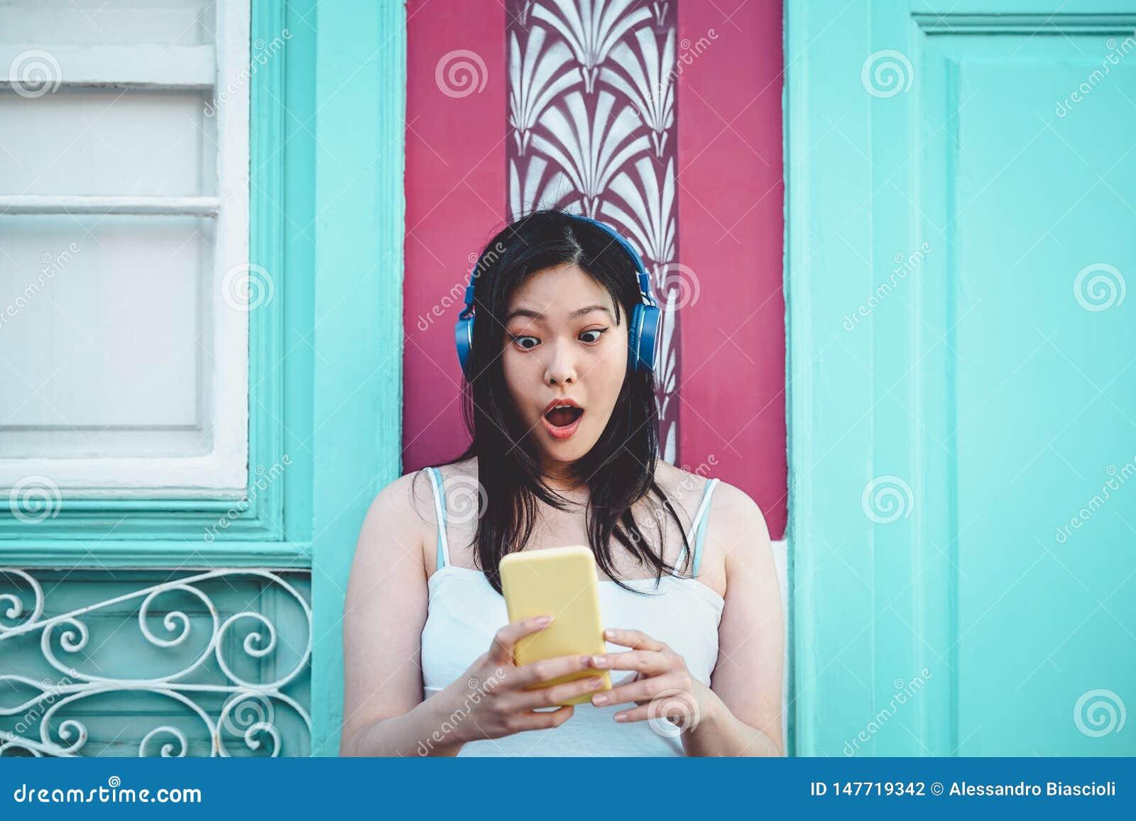 Fille asiatique heureuse ?coutant la musique avec des ?couteurs ext?rieurs - jeune femme chinoise jouant sa musique pr?f?r?e de p