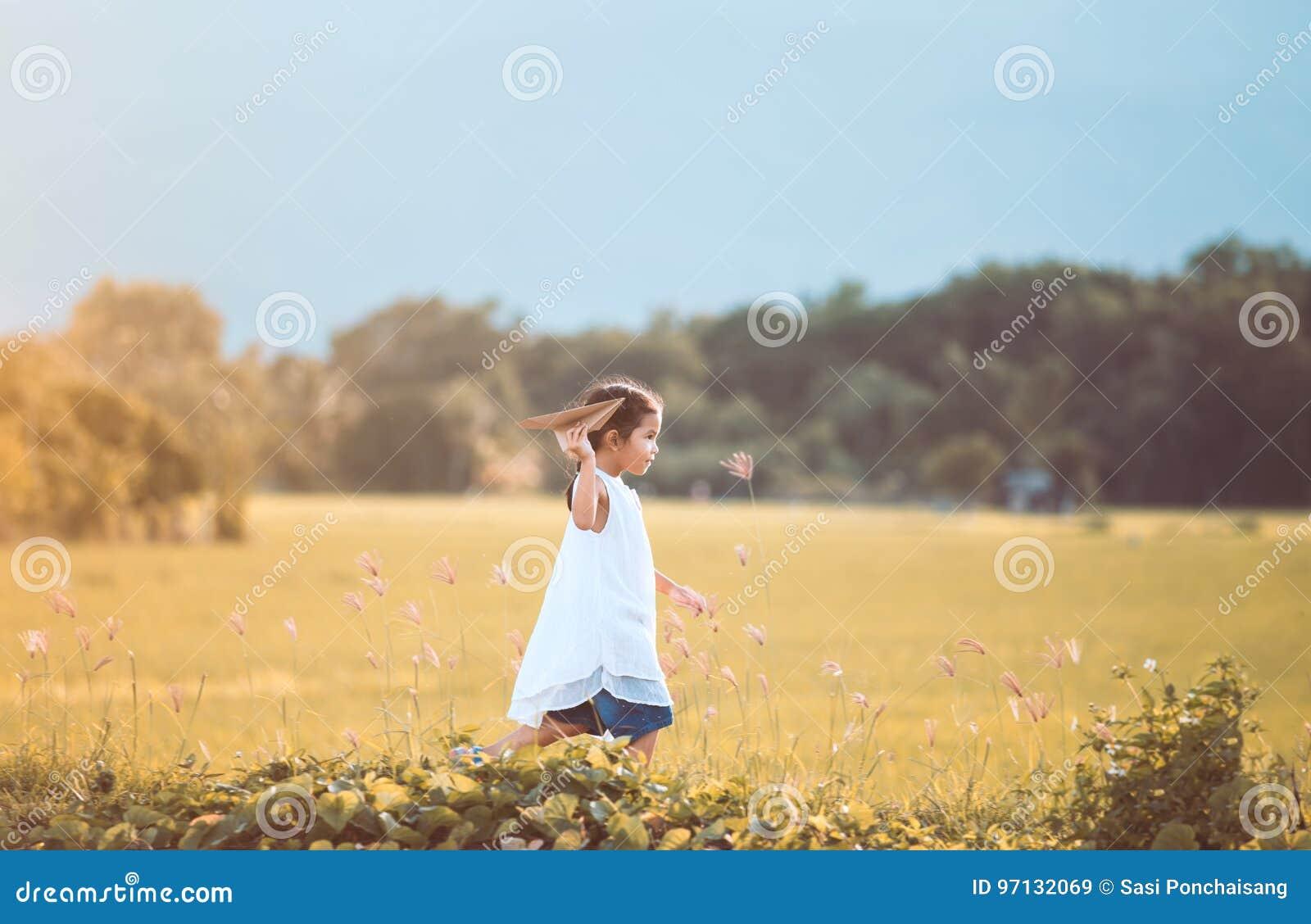 Fille asiatique mignonne d enfant courant et jouant l avion de papier de jouet