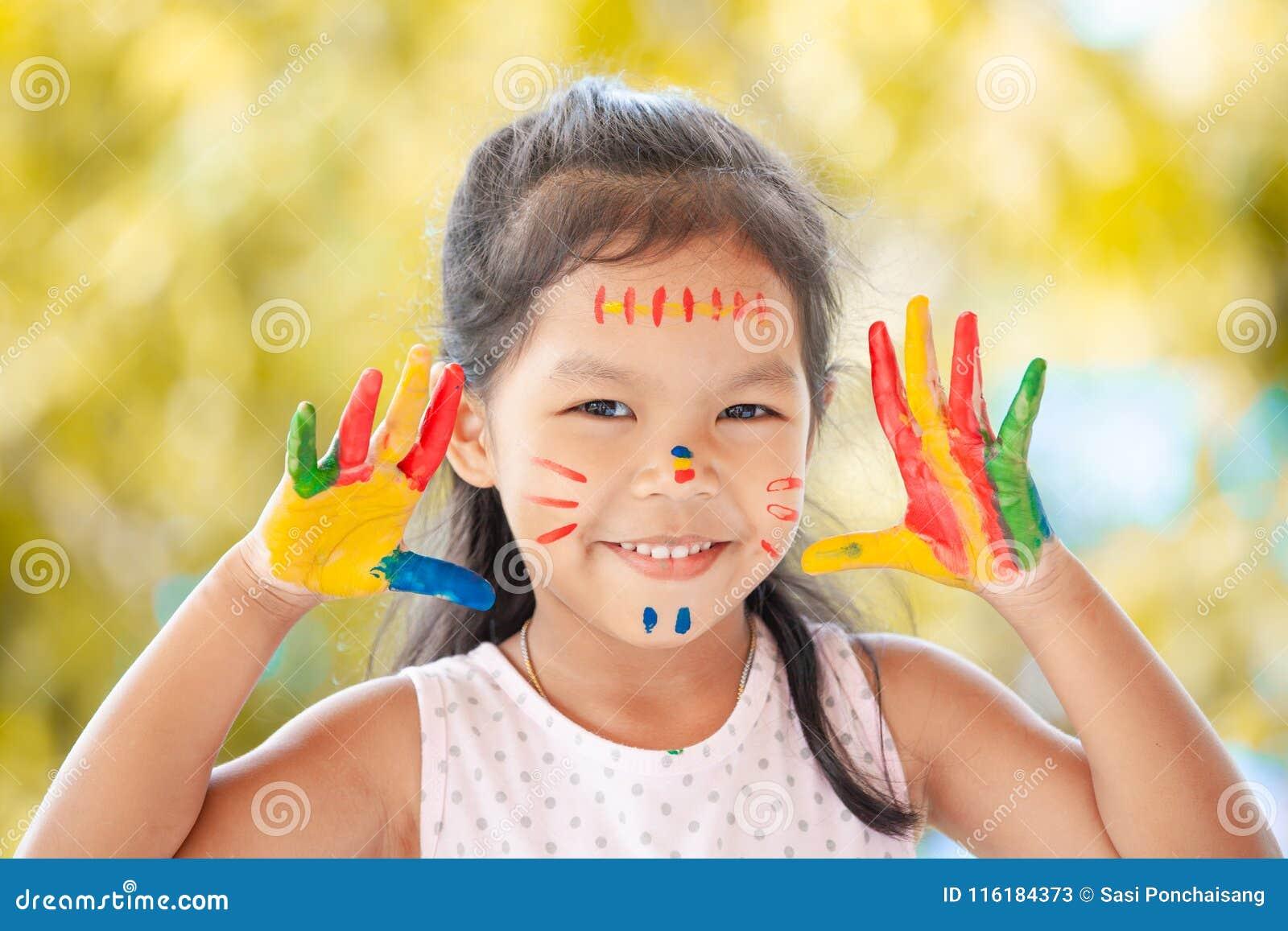 Fille asiatique mignonne de petit enfant avec les mains peintes souriant avec l amusement