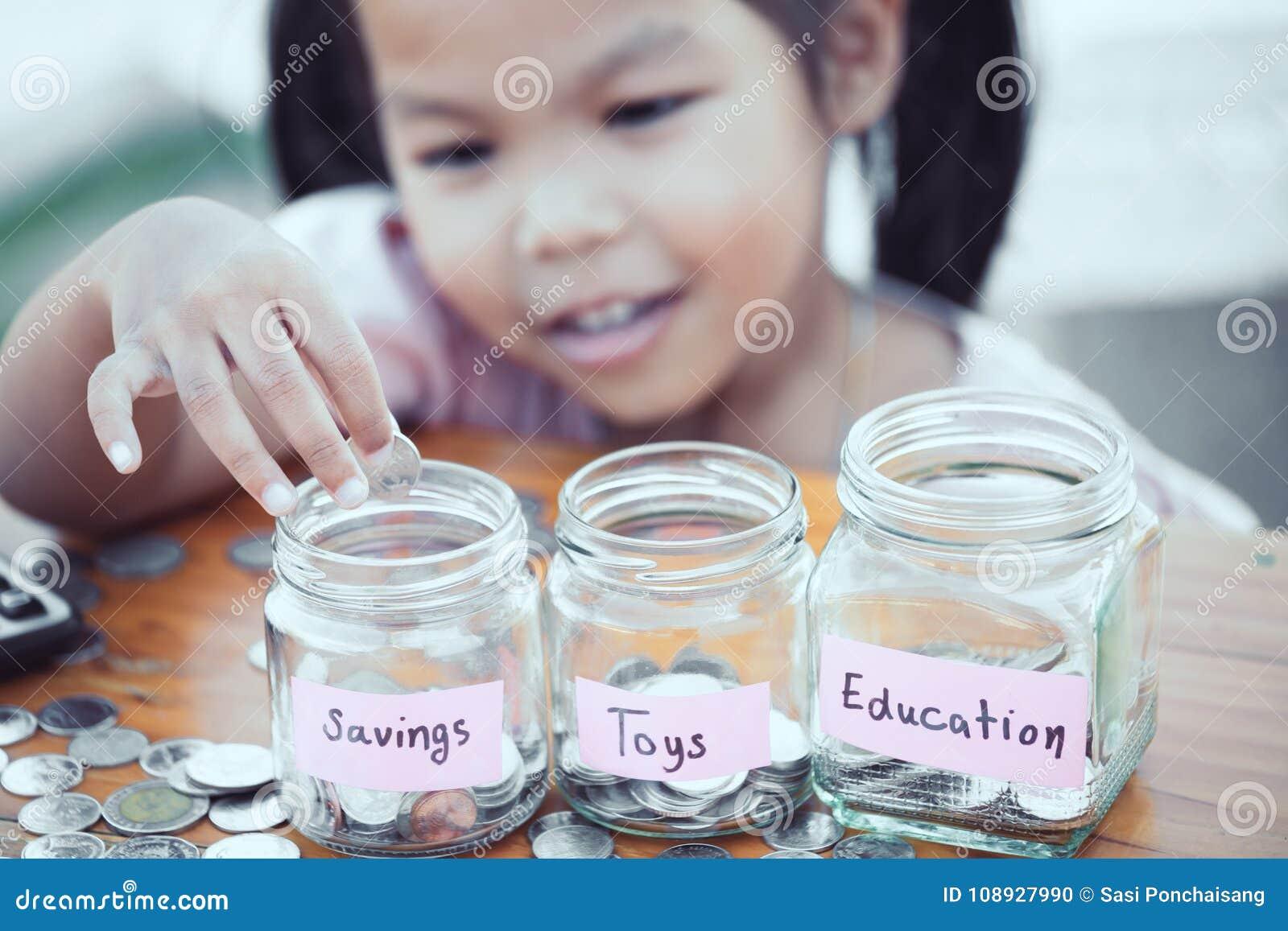 Fille asiatique mignonne de petit enfant mettant la pièce de monnaie dans la bouteille en verre