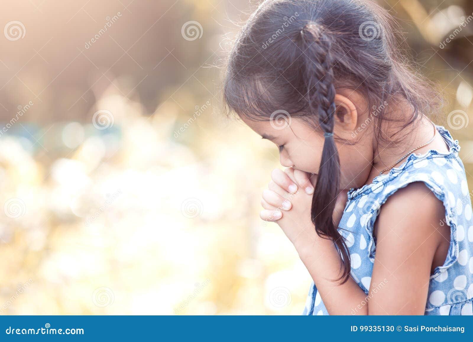 Fille asiatique mignonne de petit enfant priant avec plié sa main
