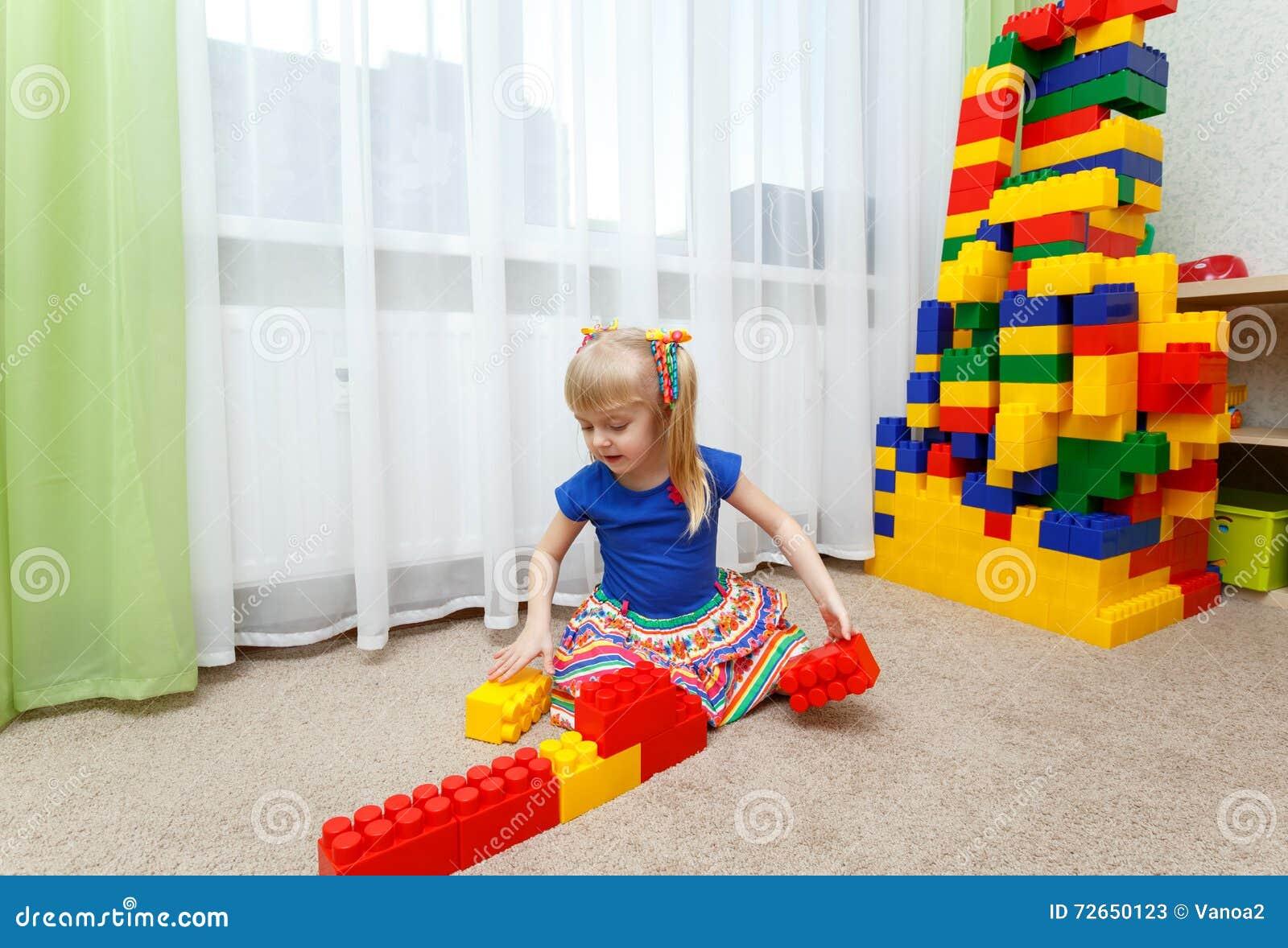 Fille assez blonde jouant avec les blocs colorés dans le jardin d enfants