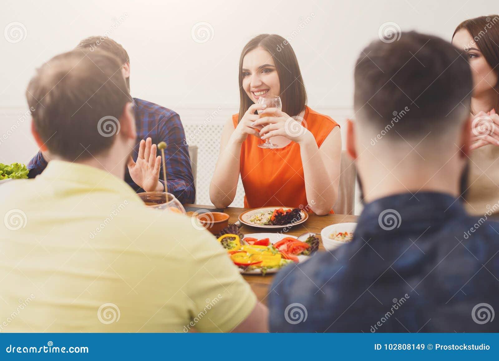 Fille assez heureuse avec des amis au dîner de fête de table