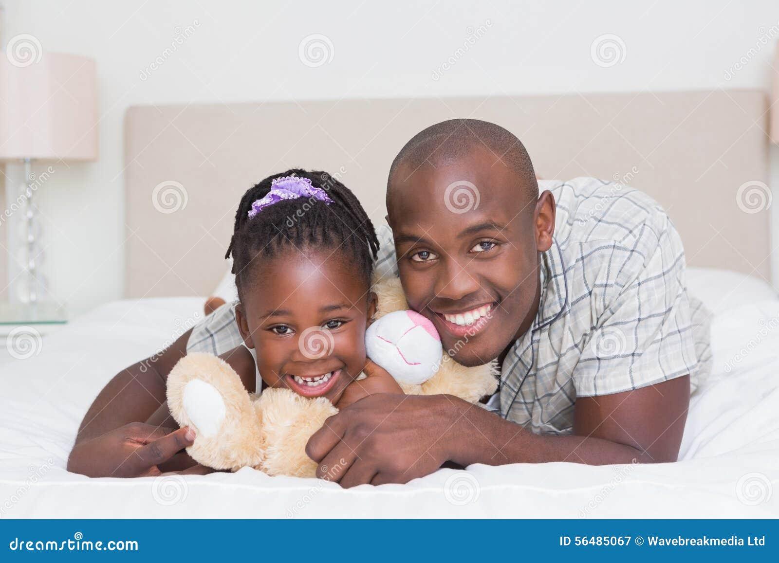 Fille assez petite avec son père dans le lit