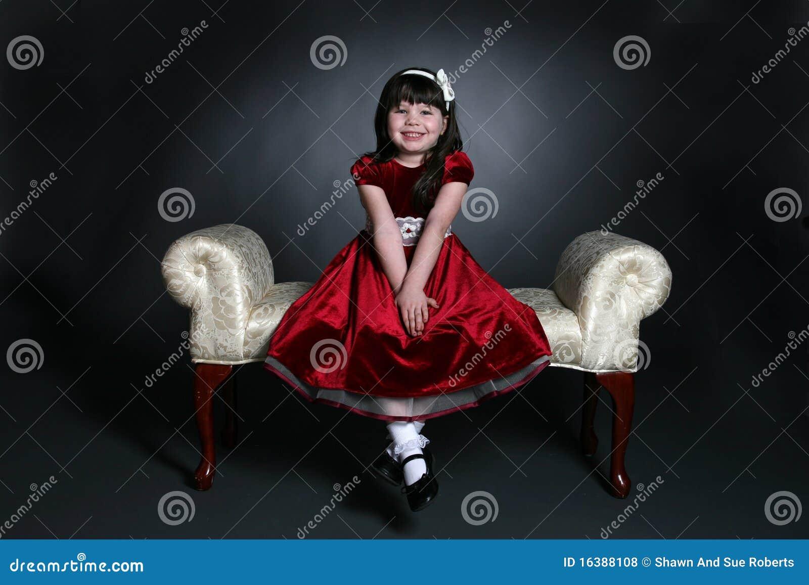 Fille assez petite dans la robe rouge de vacances