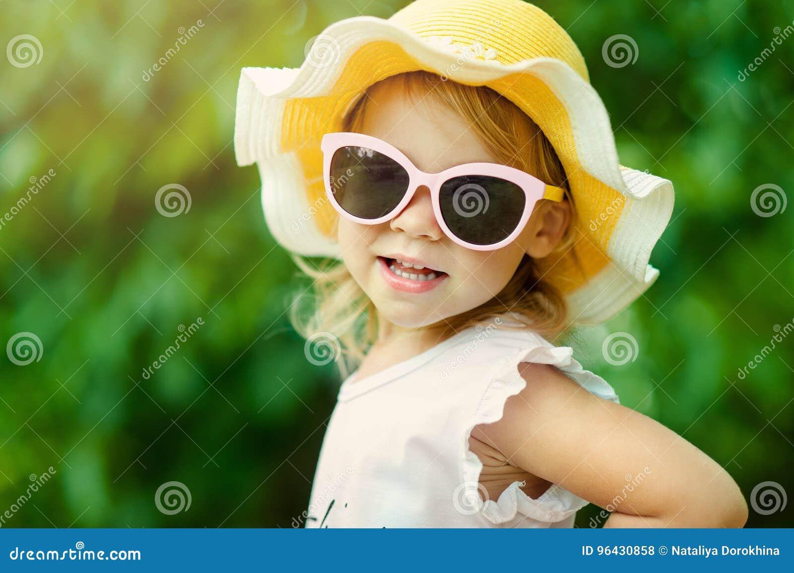 Fille assez petite dans une robe et un chapeau rayés détendant sur la plage près de la mer, été, vacances, concept de voyage Sour