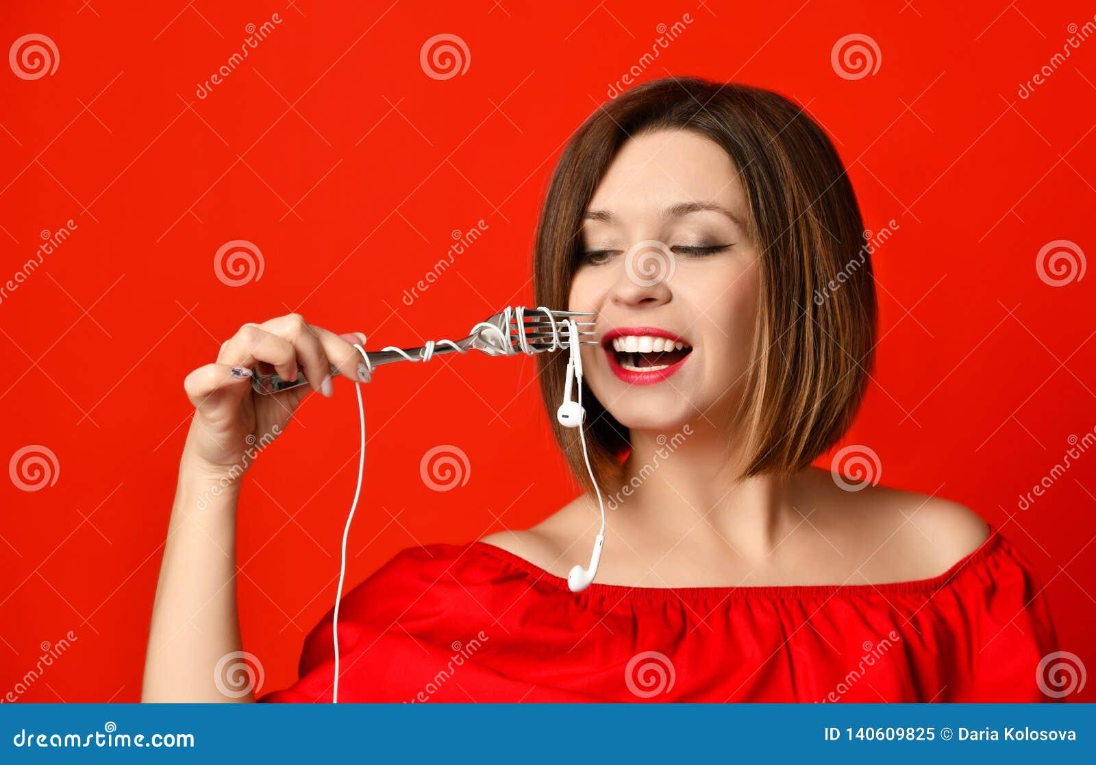Fille attirante dans la robe rouge tenant une fourchette dans des mains sur la prise d écouteur A préparé pour manger