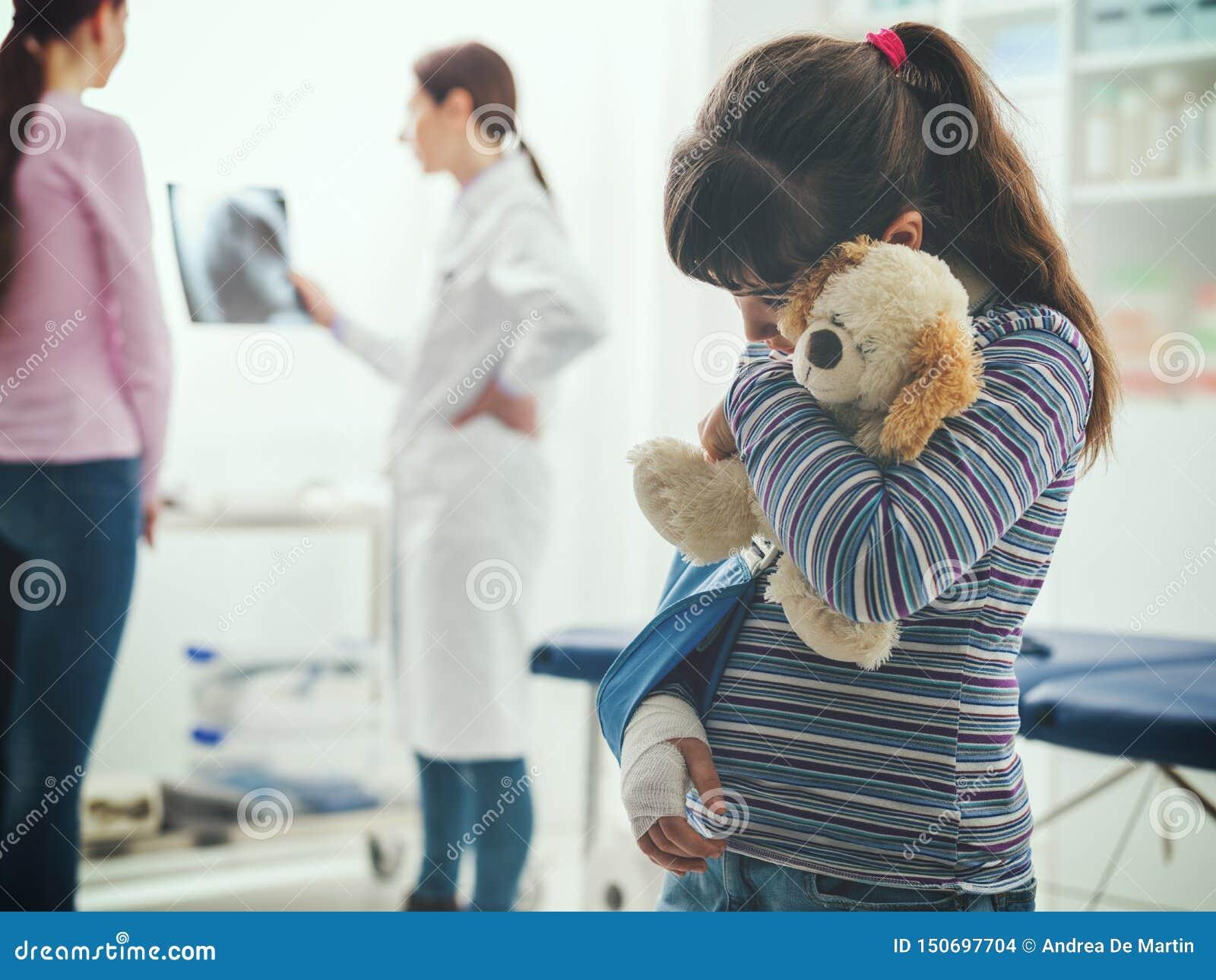 Fille avec l accolade de bras dans le bureau du docteur
