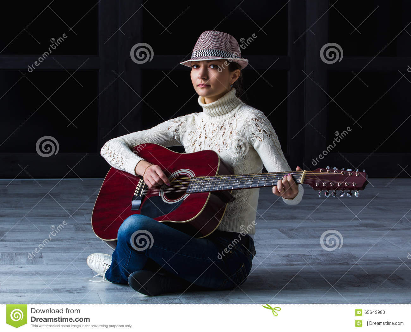 Fille avec la guitare se reposant sur le plancher