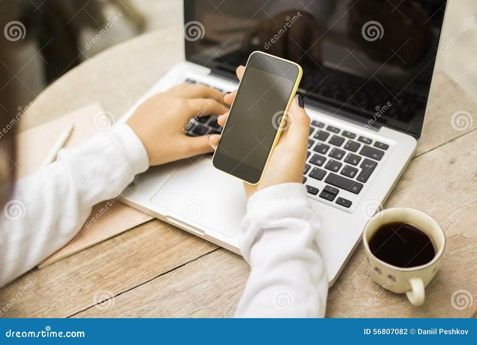 Fille avec le téléphone portable, l ordinateur portable et la tasse de café vides