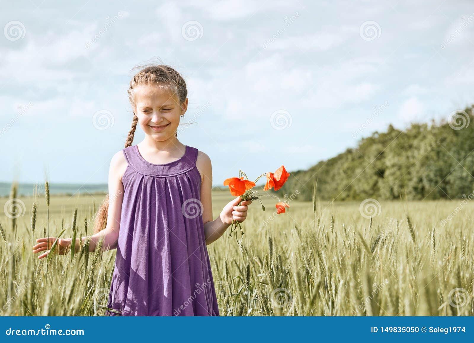 Fille avec les fleurs rouges de tulipe posant dans le domaine de bl?, le soleil lumineux, beau paysage d ?t?