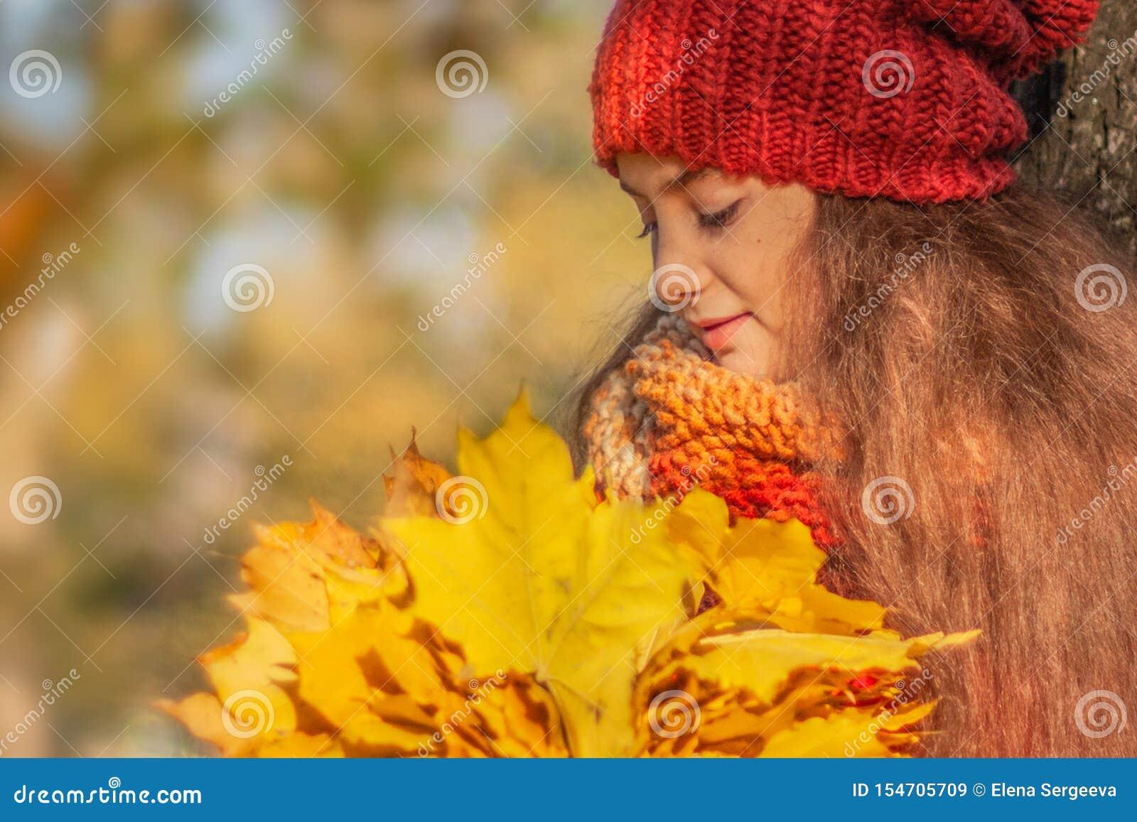 Fille avec un bouquet des feuilles en parc d automne