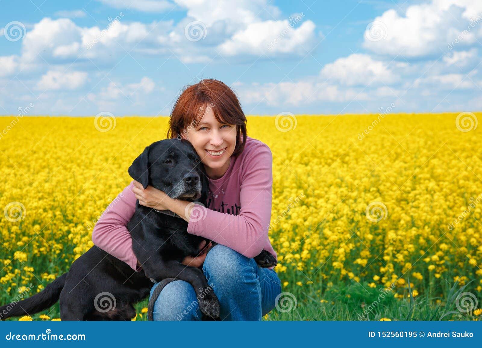 Fille avec un chien sur le champ du viol fleurissant jaune