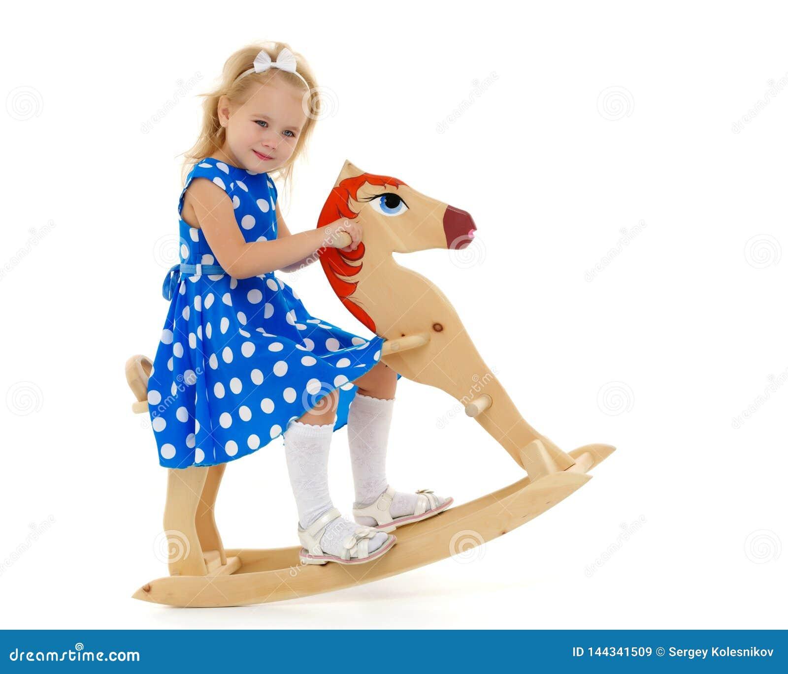 Fille balan?ant sur un cheval en bois