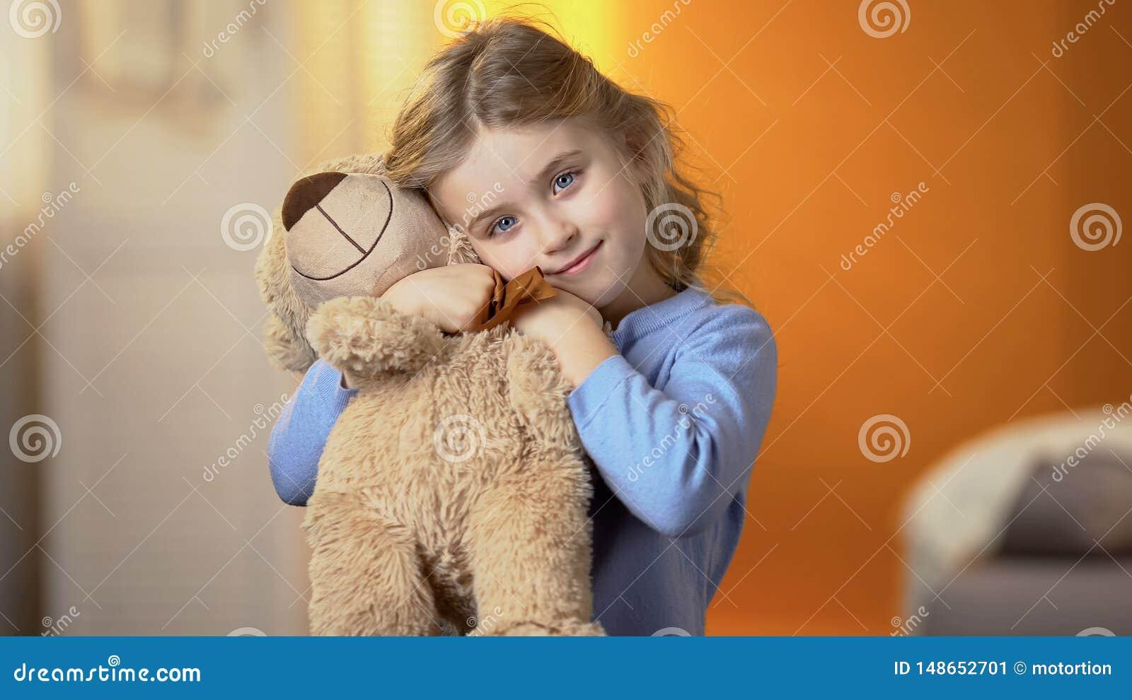 Fille blonde aux cheveux boucl?s mignonne ?treignant l ours de nounours et souriant ? la cam?ra, bonheur