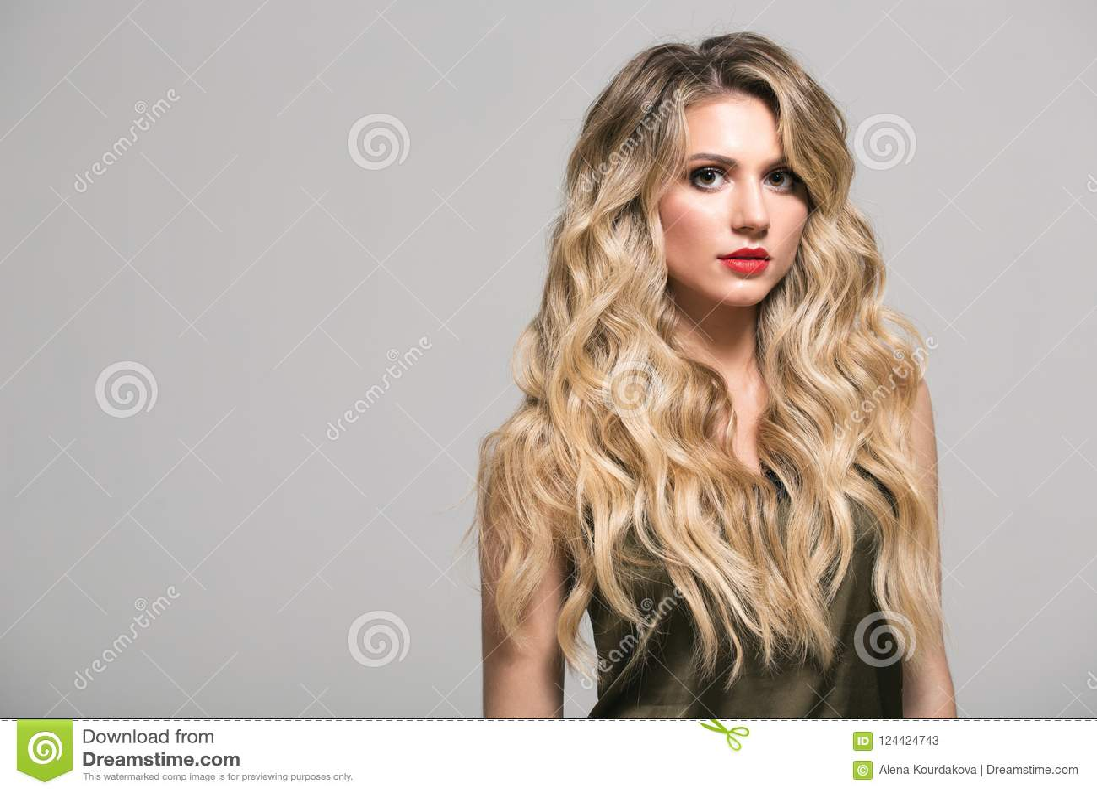Fille blonde avec longtemps et cheveux onduleux brillants de volume
