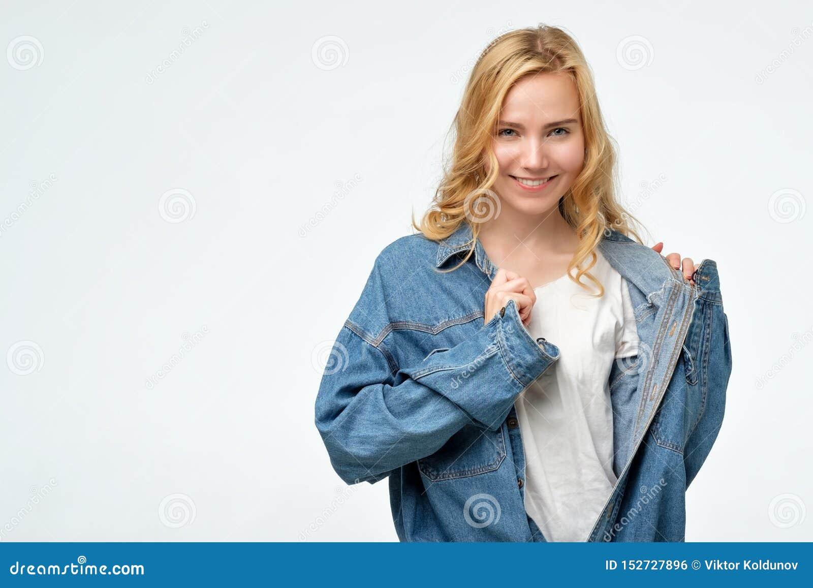 Fille blonde caucasienne effrontée positive dans la veste de jeans souriant à la caméra