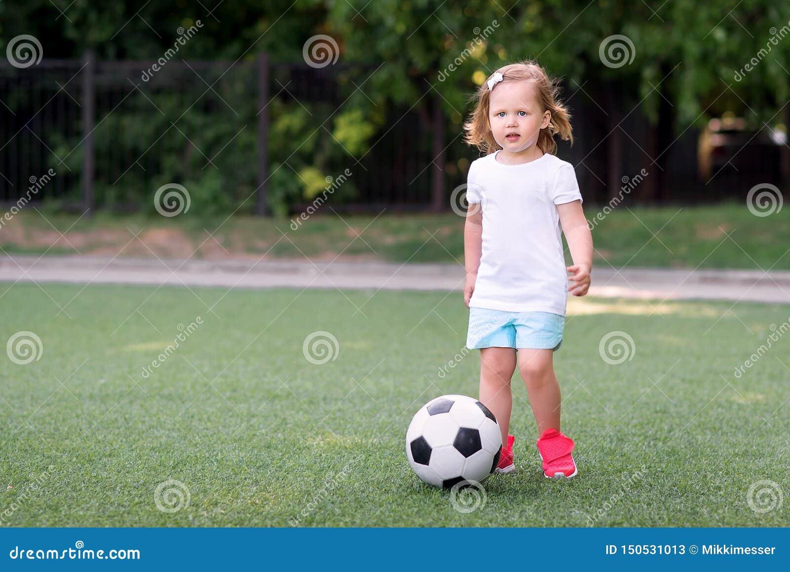 Fille blonde d enfant en bas âge dans des shorts bleus et des espadrilles roses jouant avec du ballon de football à l extérieur d