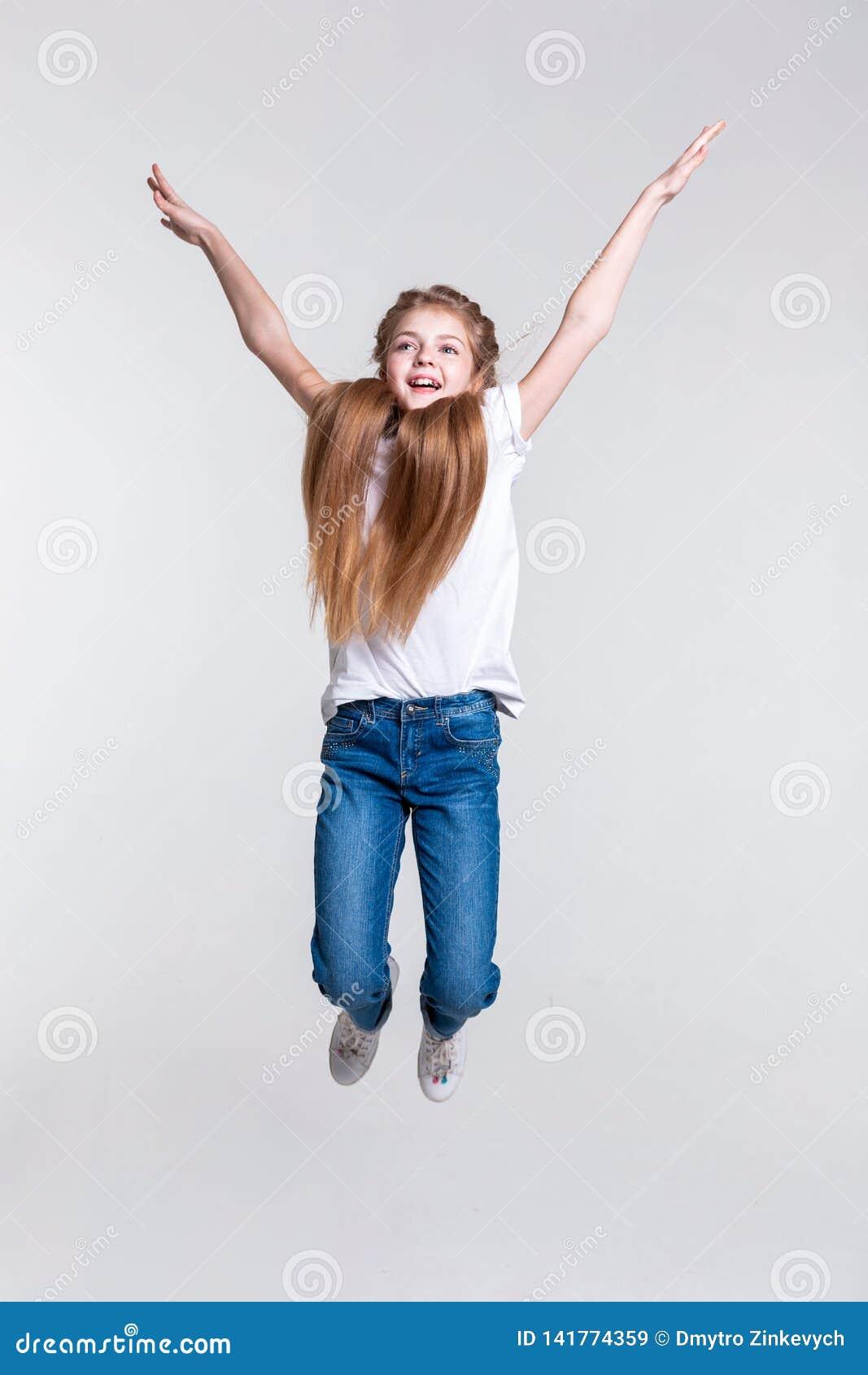 Fille blonde heureuse espiègle sautant fortement avec les mains tirées