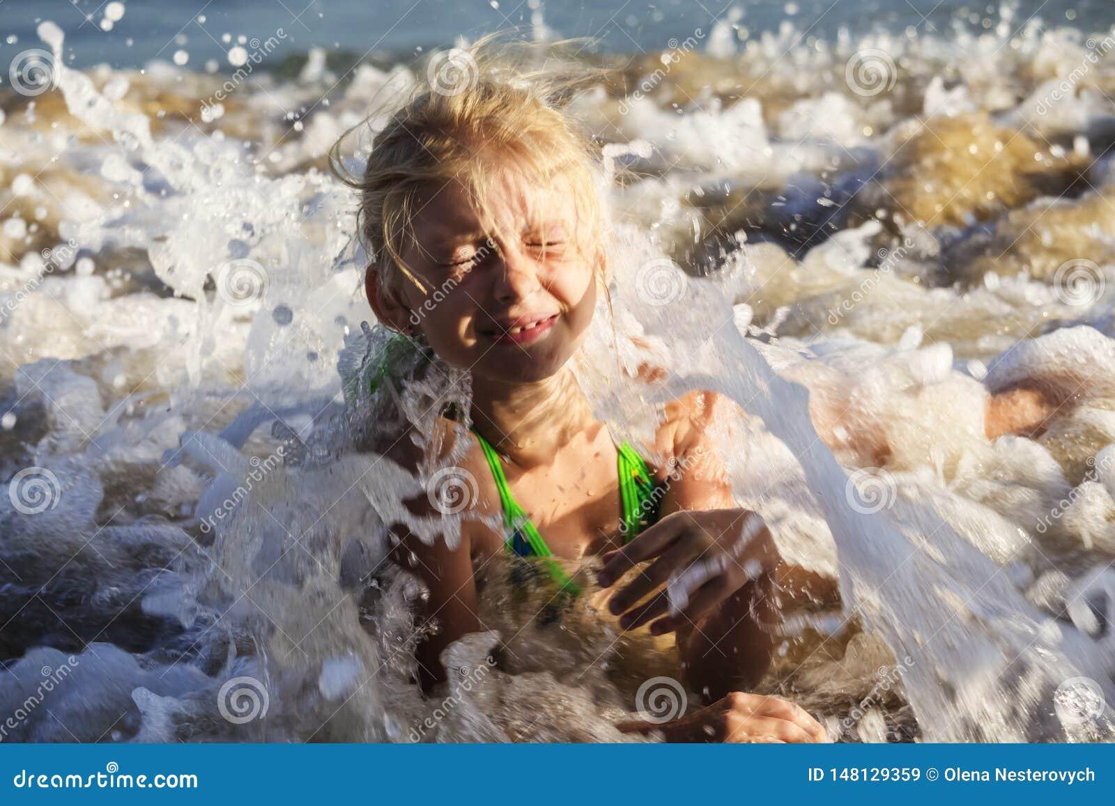 Fille blonde heureuse et belle dans un maillot de bain vert se trouvant sur la plage parmi les vagues