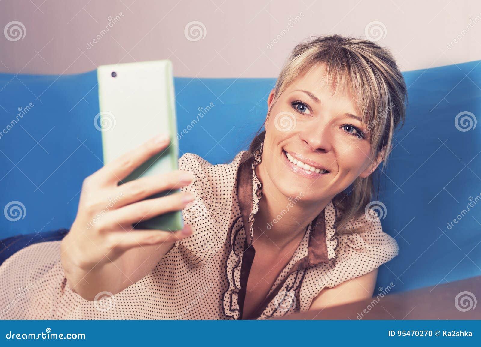 Fille blonde mignonne sur le sofa Elle regarde son smartphone et fait un selfie