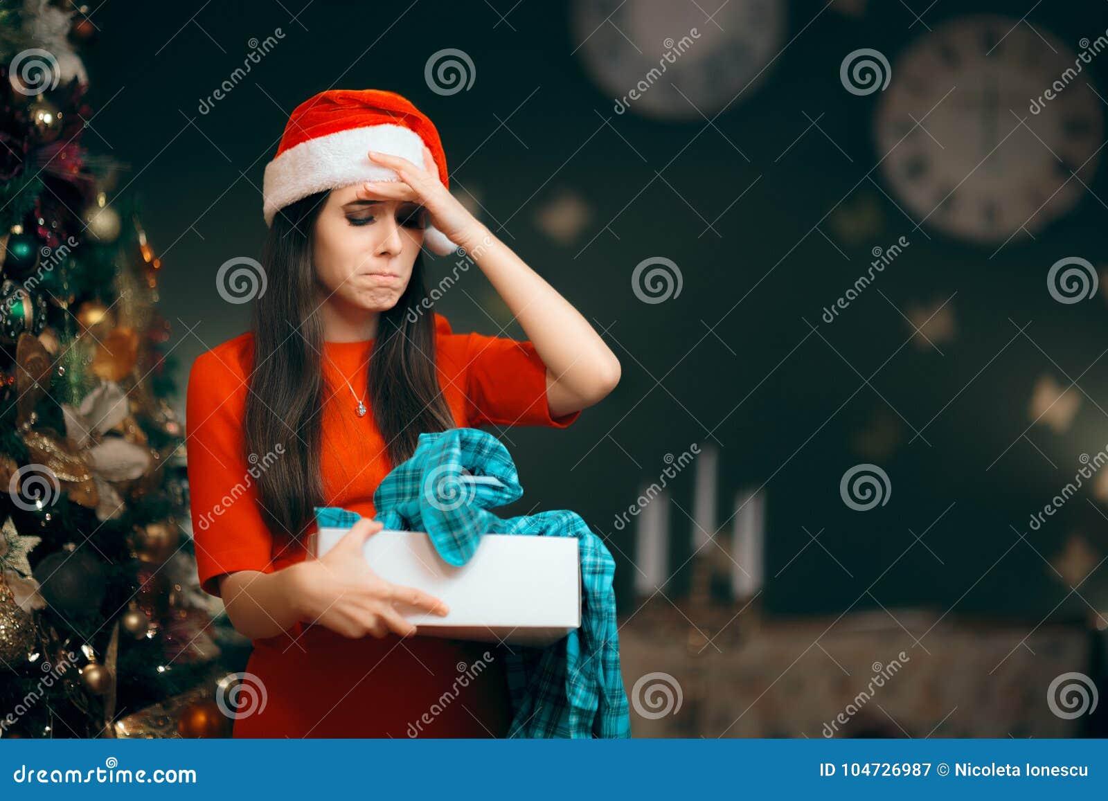 Fille bouleversée ouvrant un mauvais cadeau de Noël trouvant des pyjamas à l intérieur