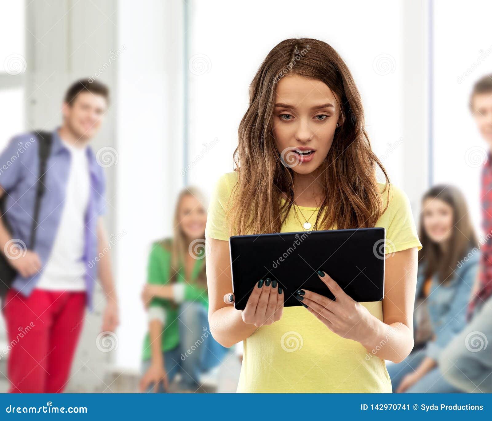 Fille choquée d étudiant avec le PC de comprimé à l école