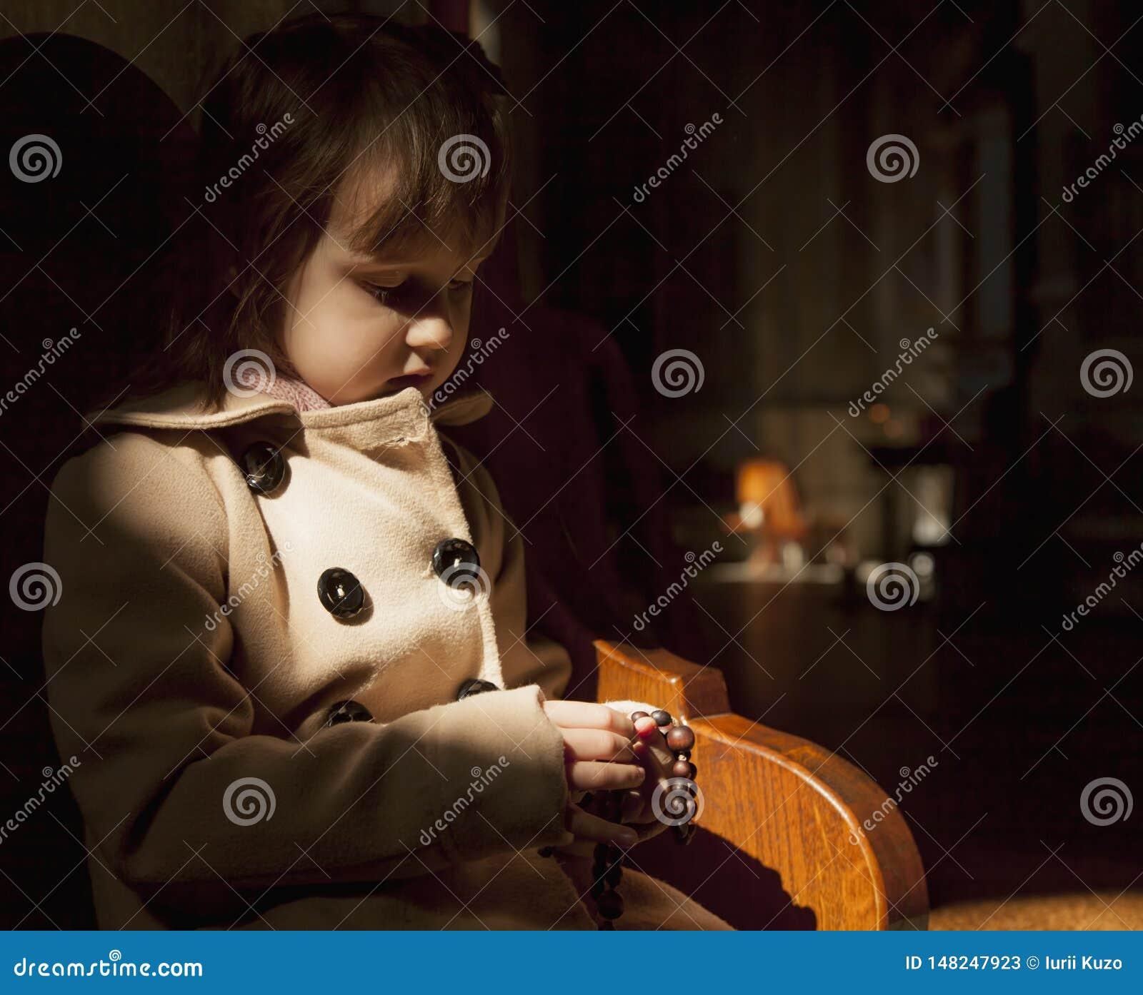 Fille chrétienne d enfant priant le chapelet foi, concept de religion