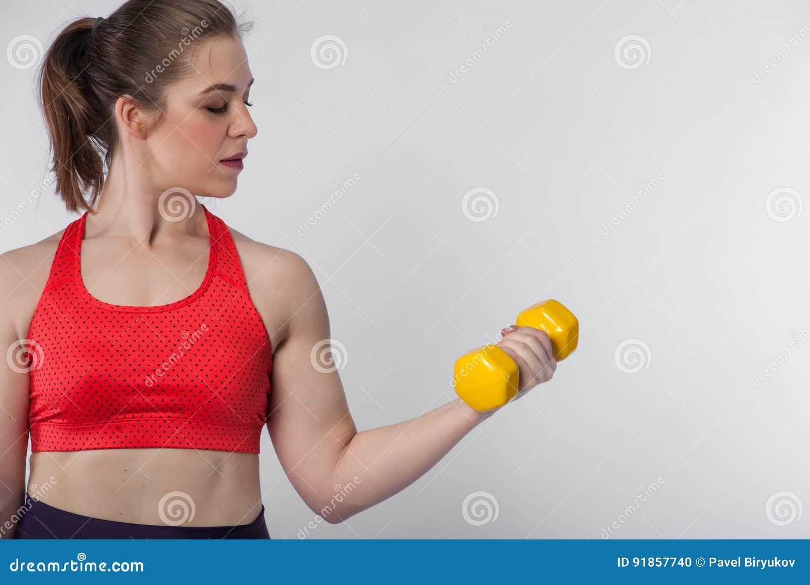 Jeune femme de brune portant l agrostide blanche posant avec l haltère jaune  sur le fond blanc Fille sportive convenable faisant l exercice de biceps ... f640994301b