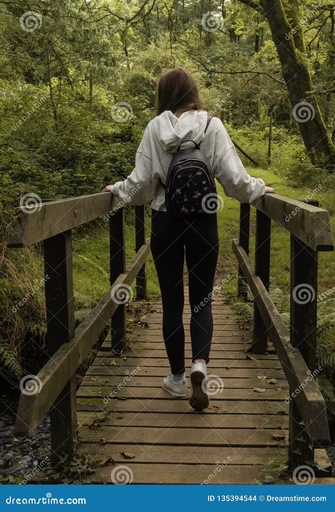 Fille croisant un pont photographié par derrière/jeune fille avec un sac à dos croisant un pont dans la forêt