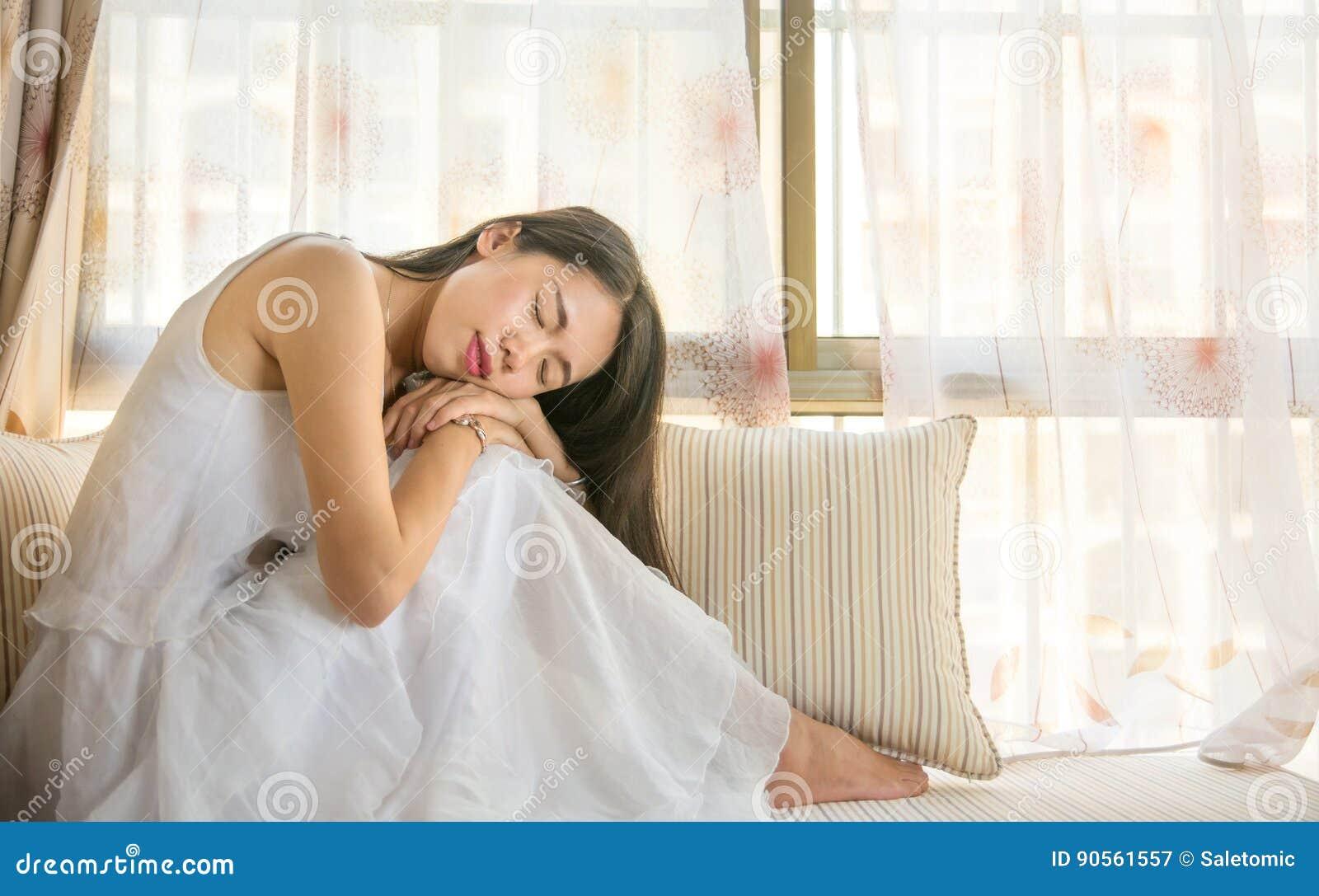Fille détendant par la fenêtre en saillie