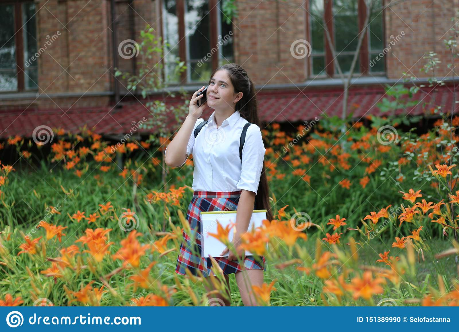 Fille d écolière avec de longs cheveux dans l uniforme scolaire parlant au téléphone
