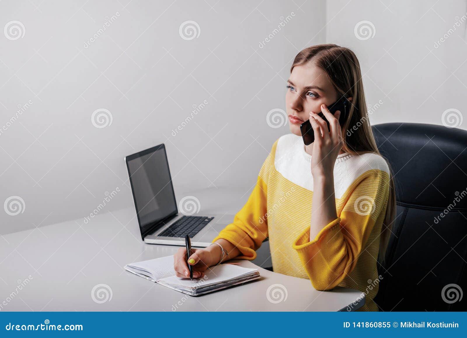 Fille d adolescent écrivant sur un bloc-notes et téléphonant tout en se reposant dans un bureau