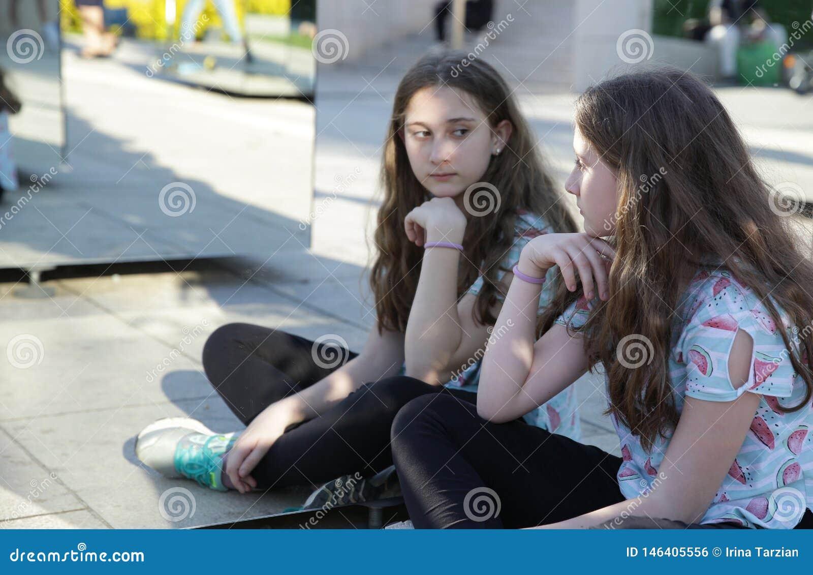 Fille d adolescent reflétée dans le miroir avec un visage sérieux se reposant en position de lotus dans le parc