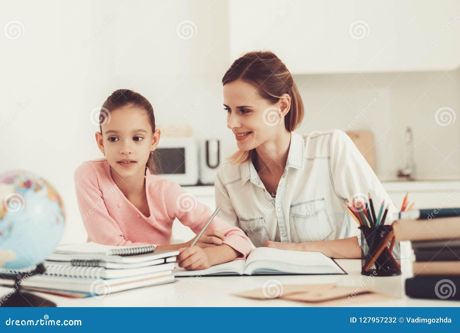 Fille daides de maman pour faire des devoirs dans la cuisine photo