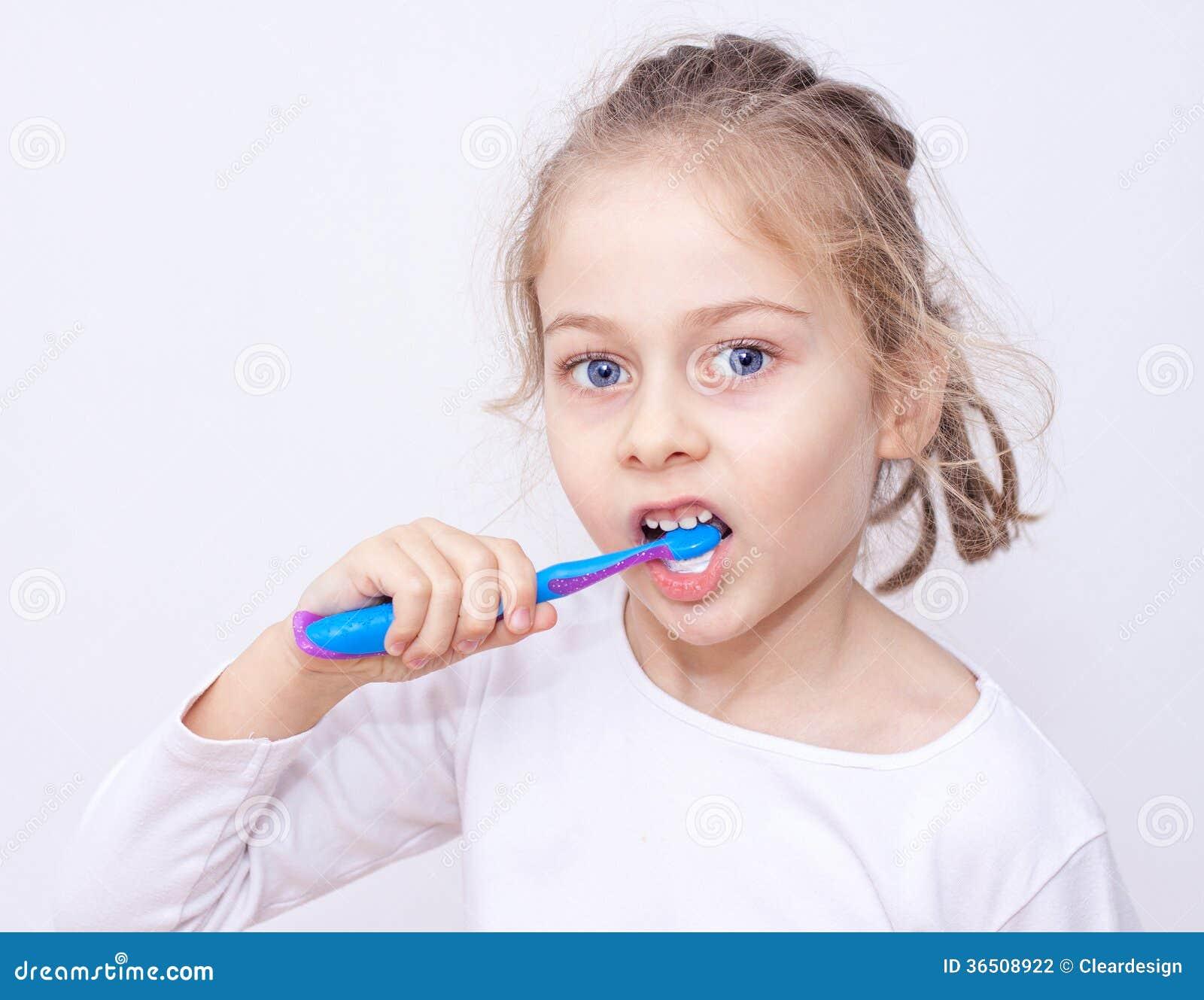 Fille d enfant dans des pyjamas brossant des dents - hygiène heure du coucher