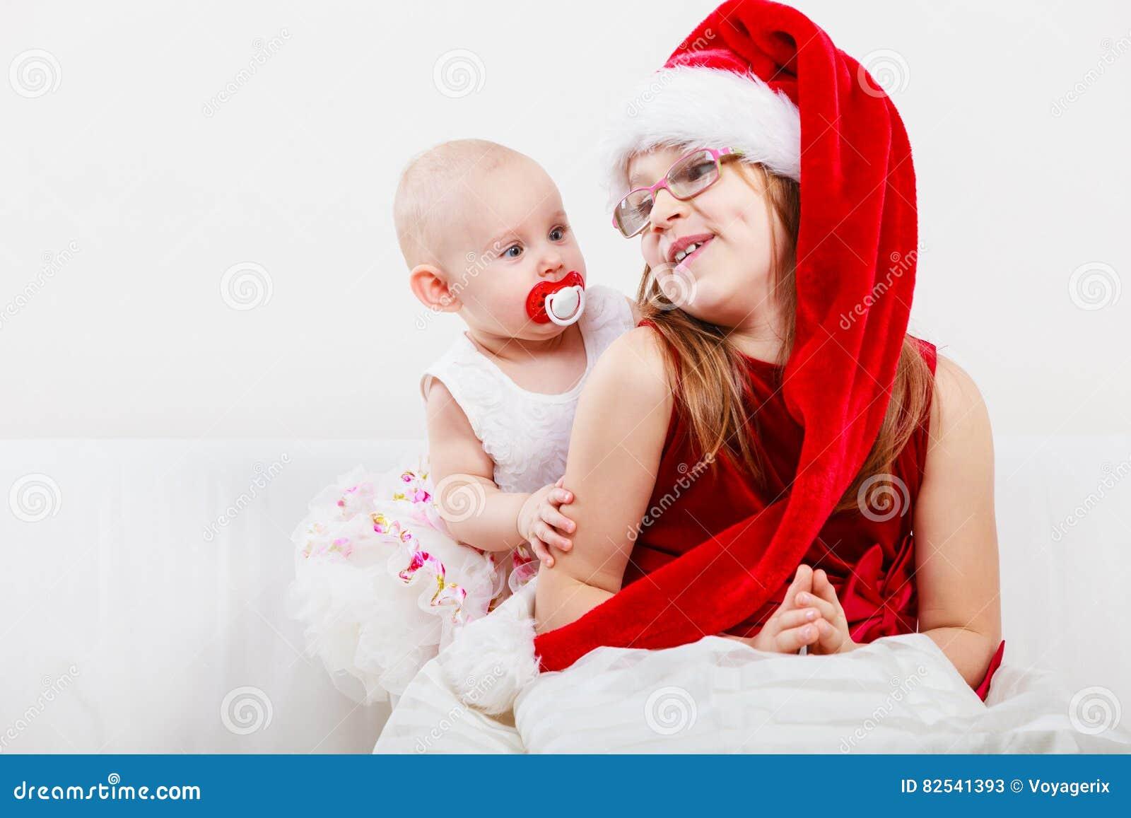 5ca8ff97131c1 Concept de vacances de Noël Fille d enfant en bas âge utilisant le chapeau  de Santa avec le petit bébé avec l auréole