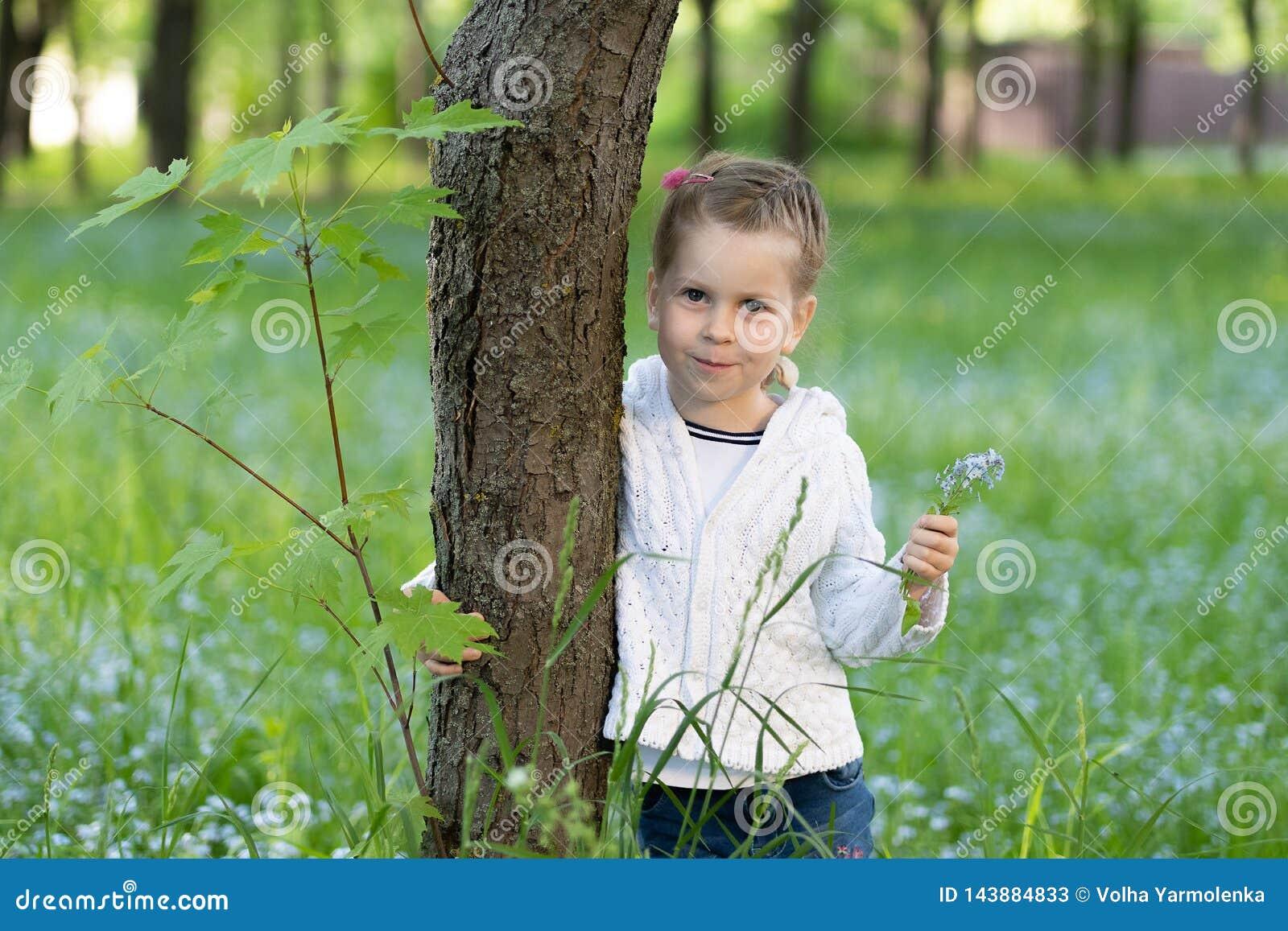 Fille d Ittle avec un groupe de myosotis des marais dans sa main jetant un coup d oeil par derrière un arbre