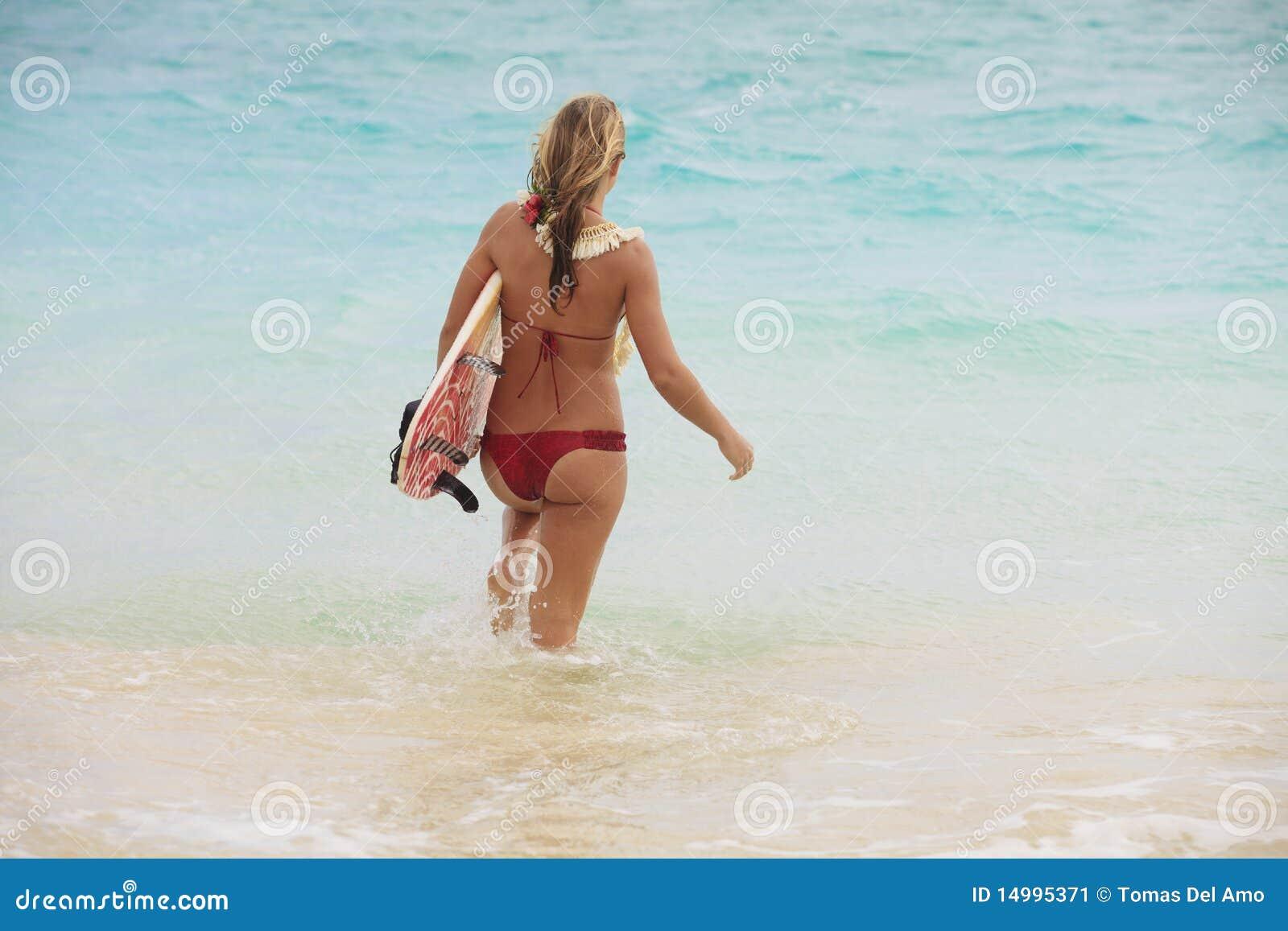 Fille dans l océan avec sa planche de surfing