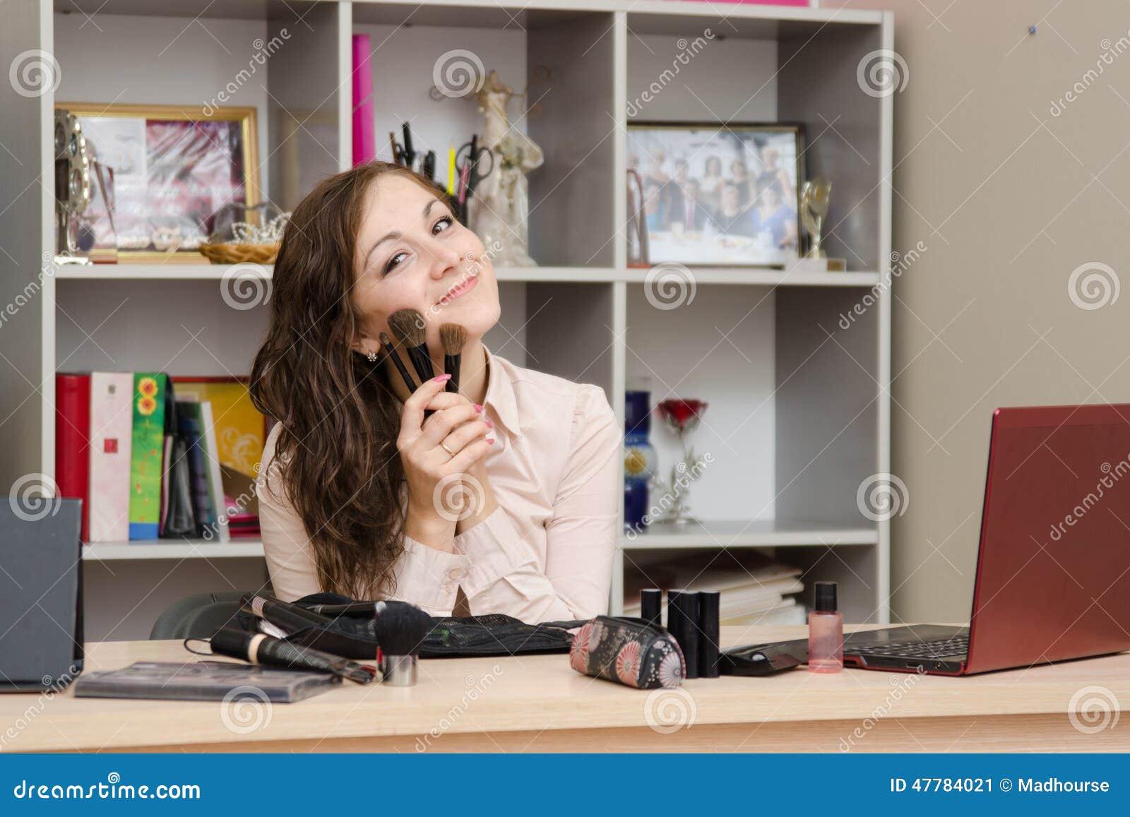 Fille dans le bureau avec des brosses pour le maquillage image