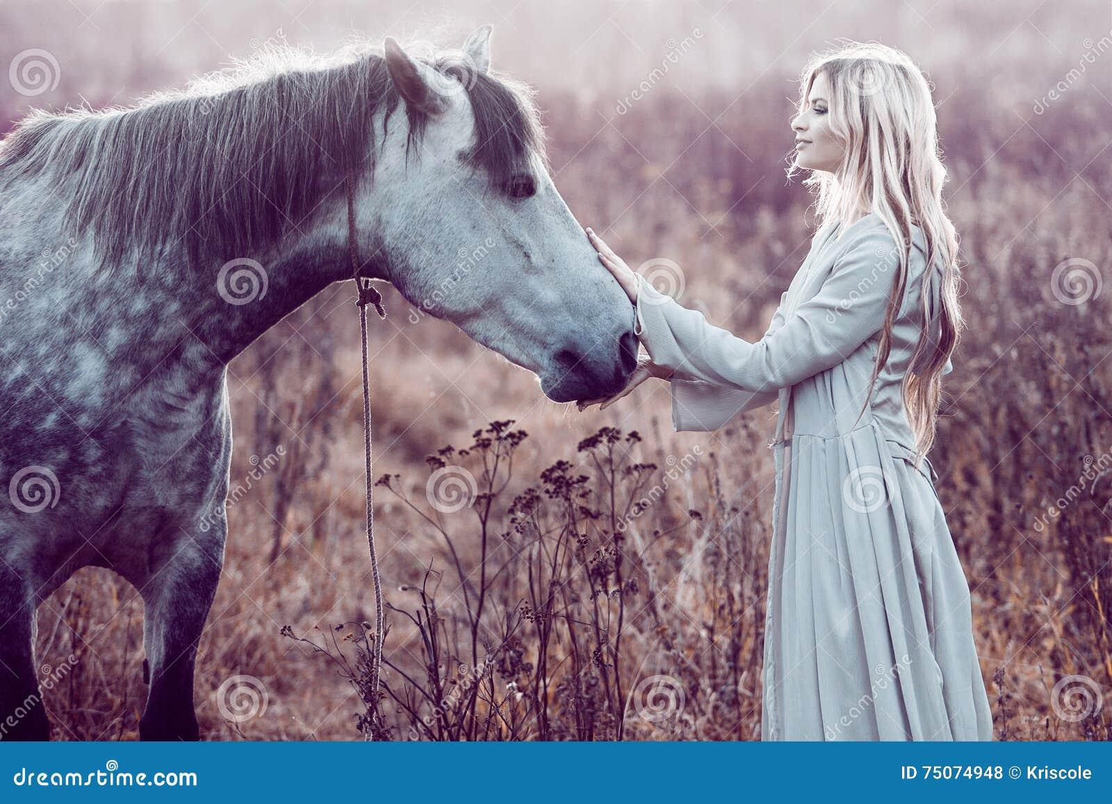 Fille dans le manteau à capuchon avec le cheval, effet de la tonalité