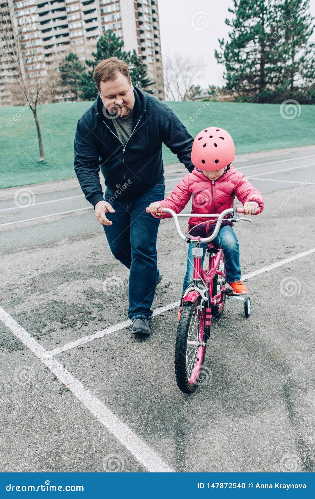 Fille de aide de fille de formation de père pour monter la bicyclette