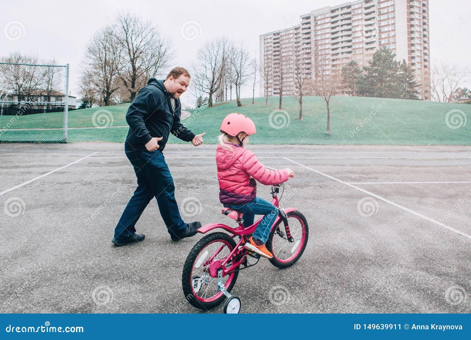 Fille de aide de sourire de fille de formation caucasienne enthousiaste de p?re pour monter la bicyclette