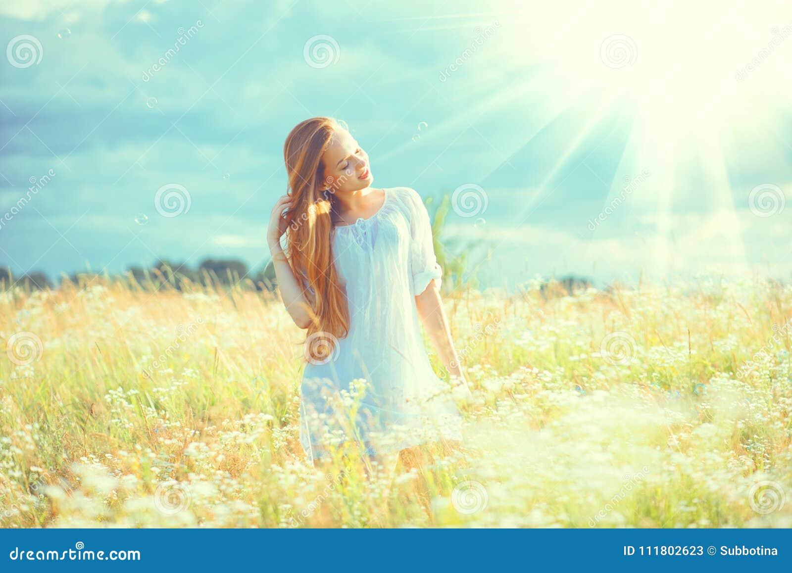 Fille de beauté appréciant dehors la nature Belle fille modèle adolescente avec de longs cheveux sains dans la robe blanche