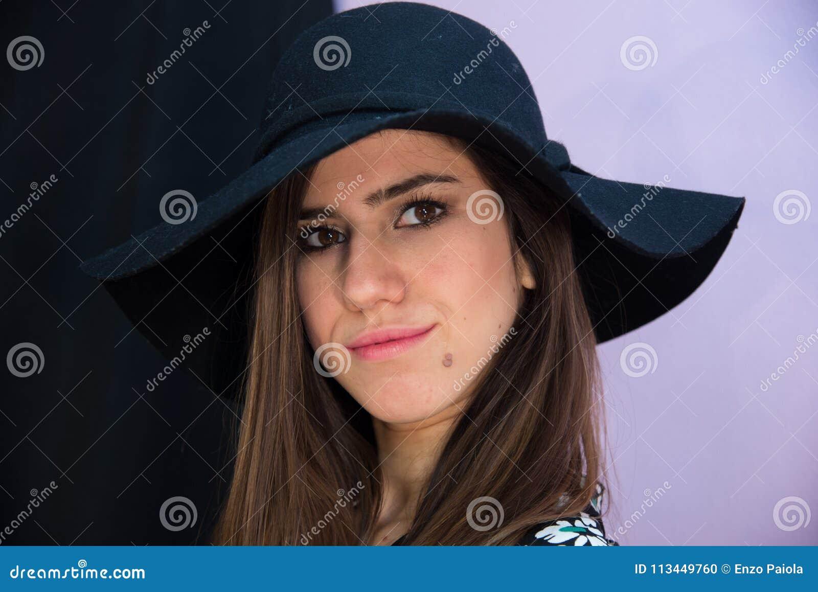Fille de brune avec de longs cheveux et chapeau, avec des marguerites de robe florale