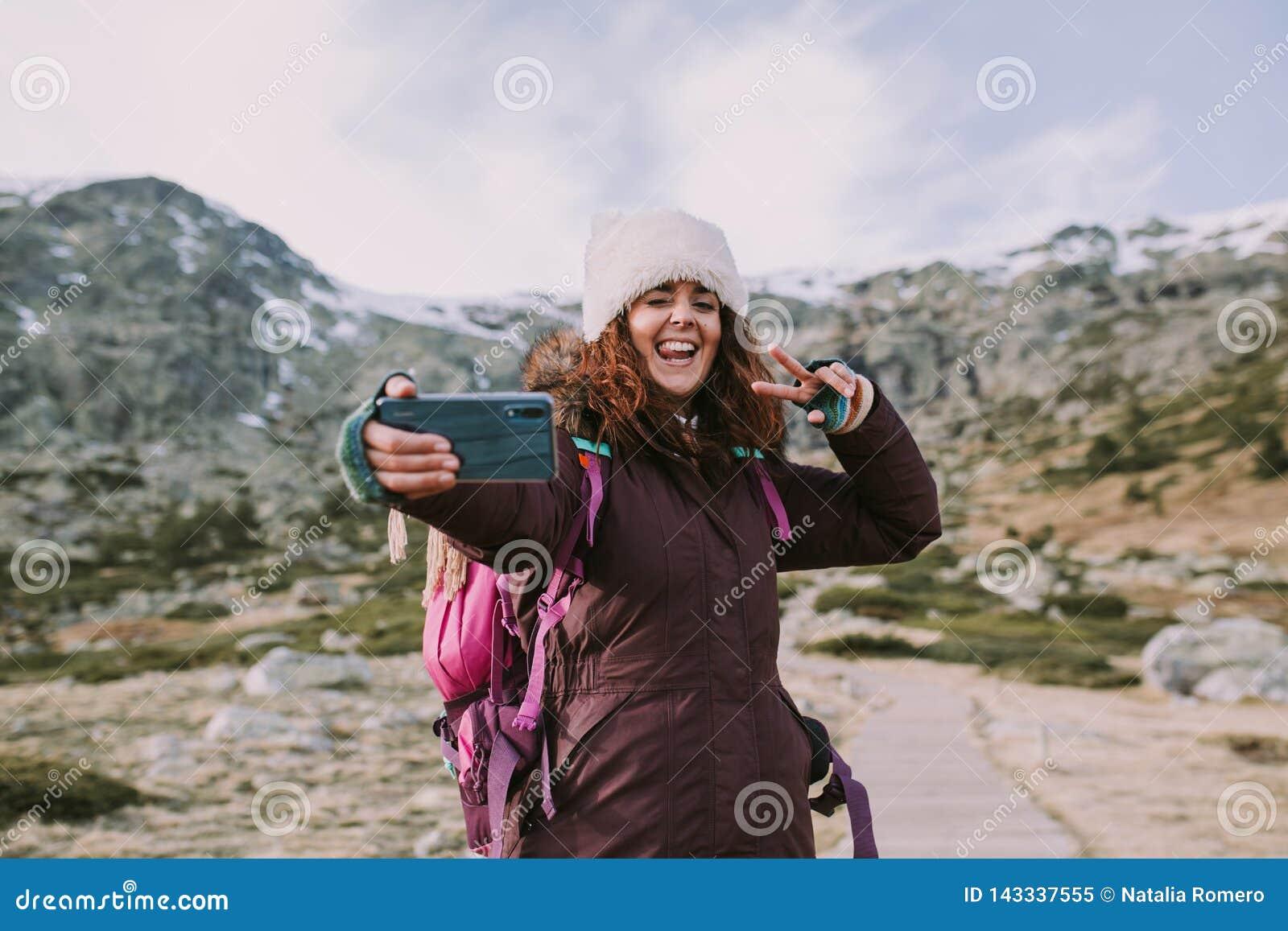 Fille de brune avec son sac à dos et un chapeau sur sa tête elle prend une photo à côté des montagnes avec un grand sourire sur s